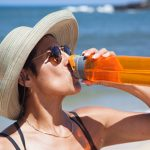 Woman Drinking water at beach with ocean in background