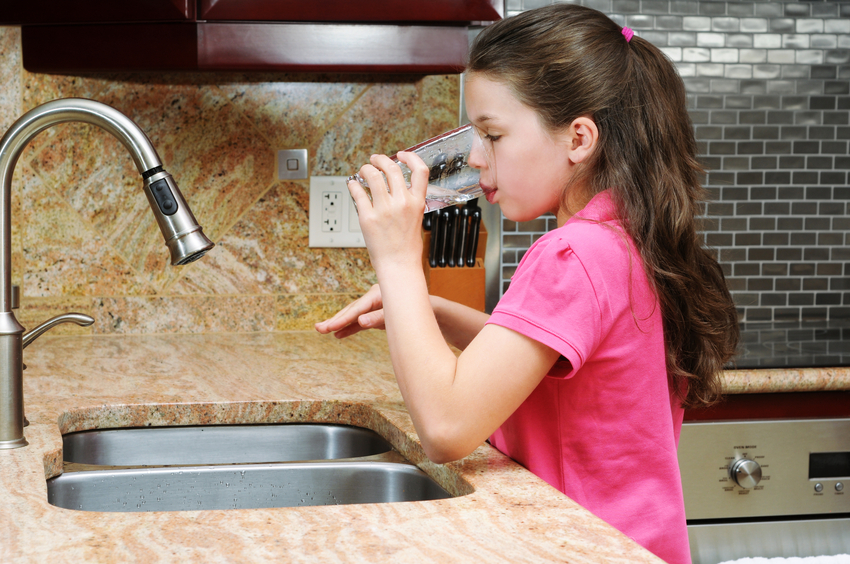 Girl drinking a glass of water in the kitchen.