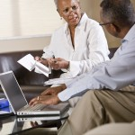 Senior African American couple paying bills online using laptop on living room couch