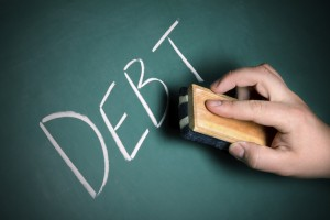 "A hand moves to erase the word ""Debt"" from a chalkboard."