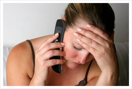 Woman on phone with hand on forehead