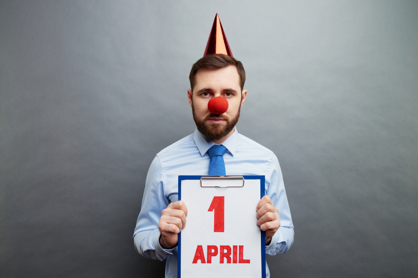 Businessman wearing clown's nose and party hat showing April fools day date