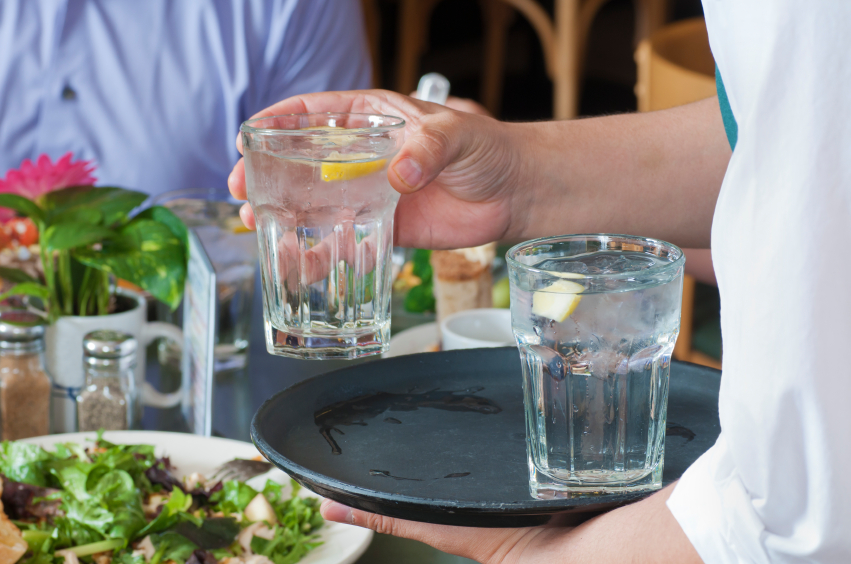 Waiter holding tray with tap water handing to customer