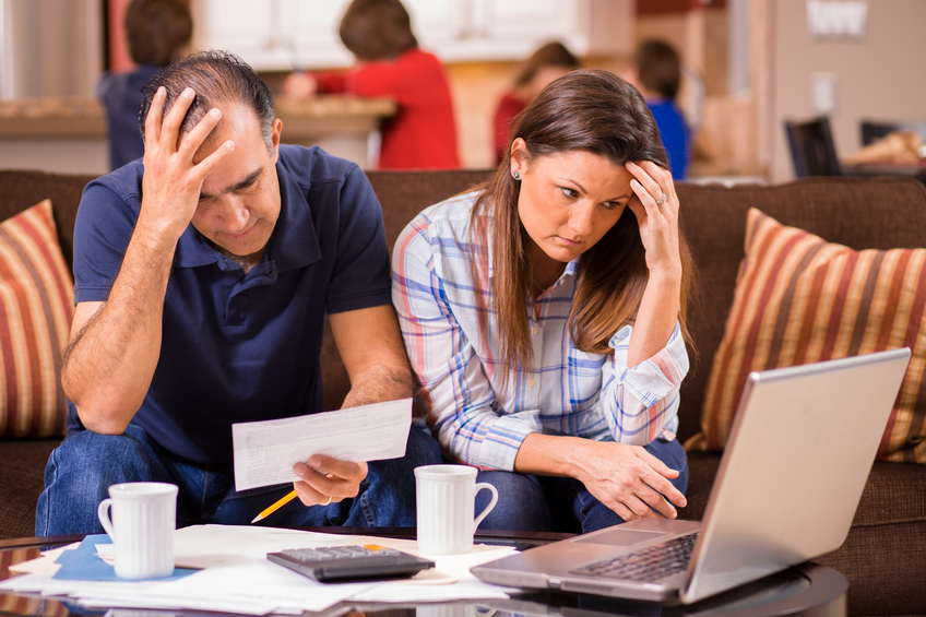 Latin descent man and woman struggle to pay their monthly bills.