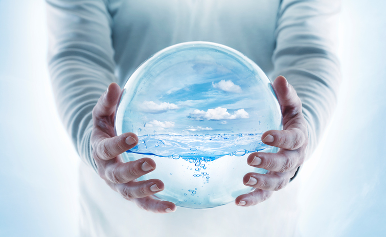 Transparent globe with water in human hands.