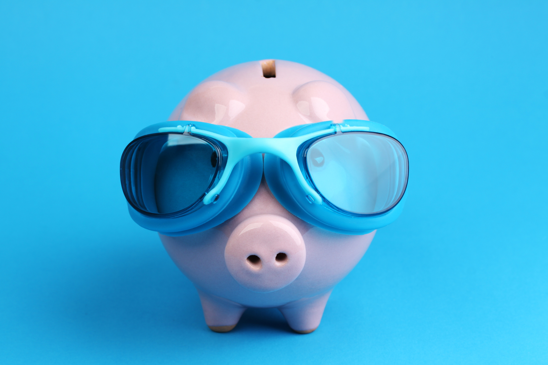 Pink piggy bank with blue swimming goggles on blue background like swimmer