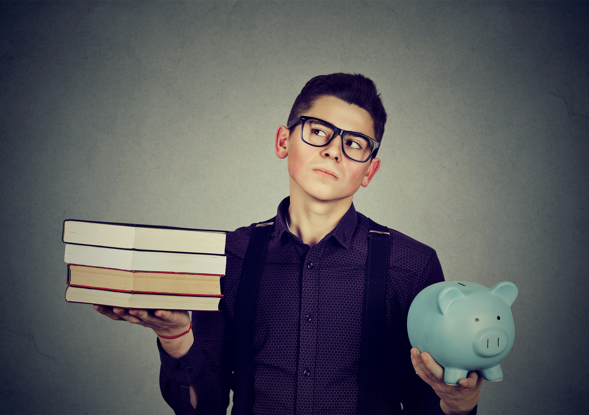 Young man with stack pile of books and piggy bank full of debt