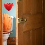 A Victorian toilet behind a half open wooden door, with love heart above