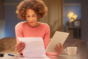 a young woman sits at home at night , going through her domestic bills and comparing them with comparison websites using her digital tablet .