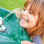 Cute and happy little girl getting water from a water fountain
