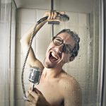 Young man is singing in the shower