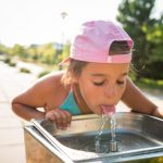Toddler drinking from the water fountain in the summertime
