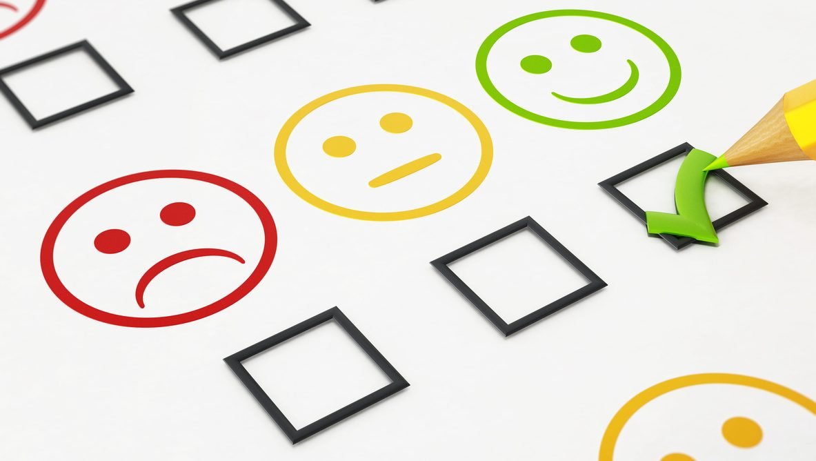 Green checkmark below smiling face symbol in a customer satisfaction survey.