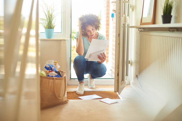 a woman returns home from the shops and finds some letters on the mat . She bends down to open them and runs her hand through her hair in despair as there is a missing bill