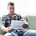 Shocked man holding a bill statement on sofa livingroom
