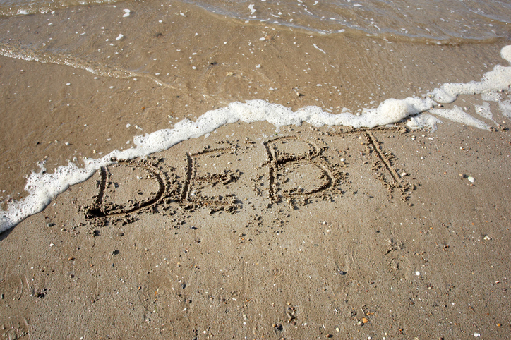 debt written on sand being washed away