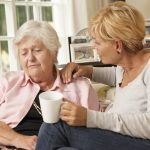 Adult Daughter Visiting Unhappy Senior Mother Sitting On Sofa At Home Trying To Comfort Her