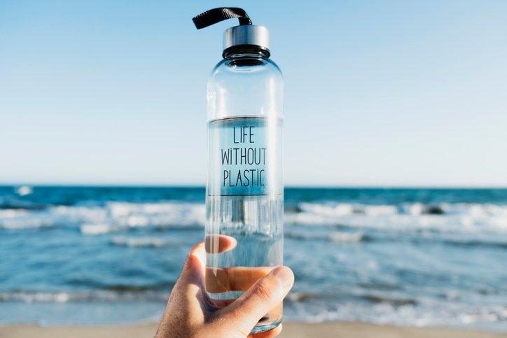Life without plastic written on a clear reusable water bottle. The water bottle is held at the beach overlooking the ocean