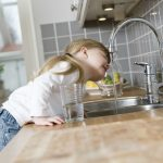 girl drinking from kitchen sink tap