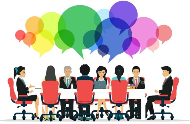 group discussion around a table with colourful speech bubbles