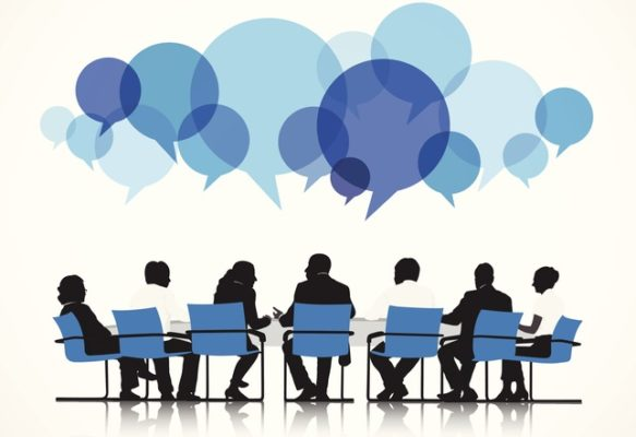 Group of People Discussing on a table with blue speech bubbles