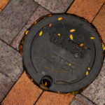 Utility water meter on a brick sidewalk.