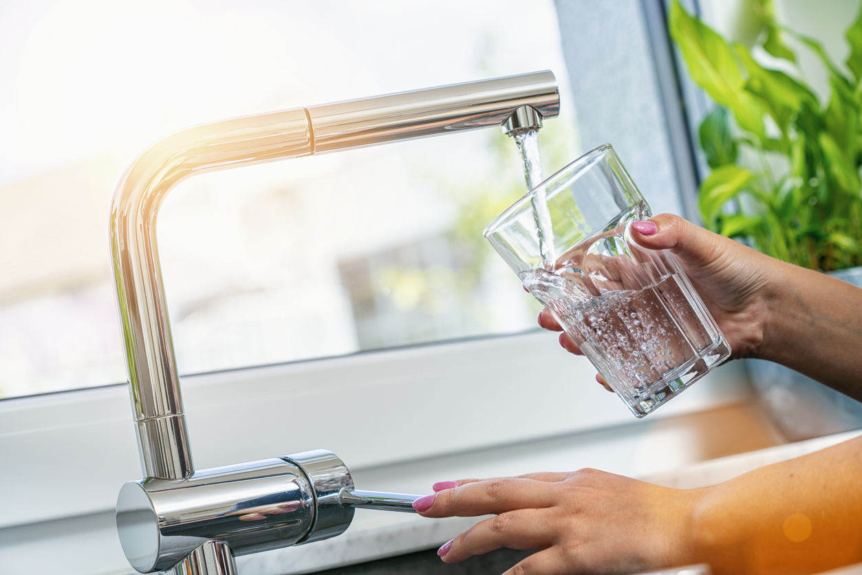 woman filling glass with water