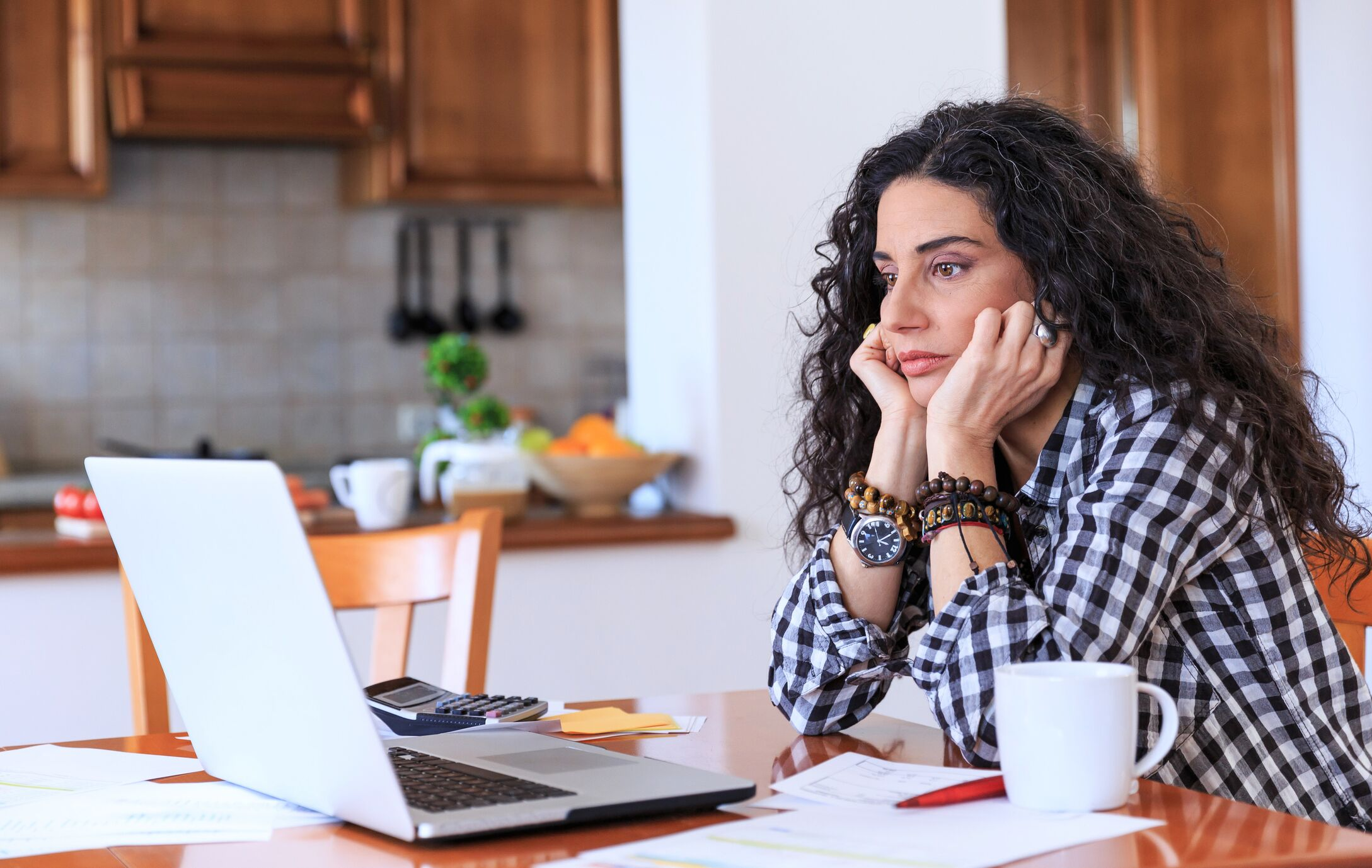 Lady looking at laptop worrying about finances