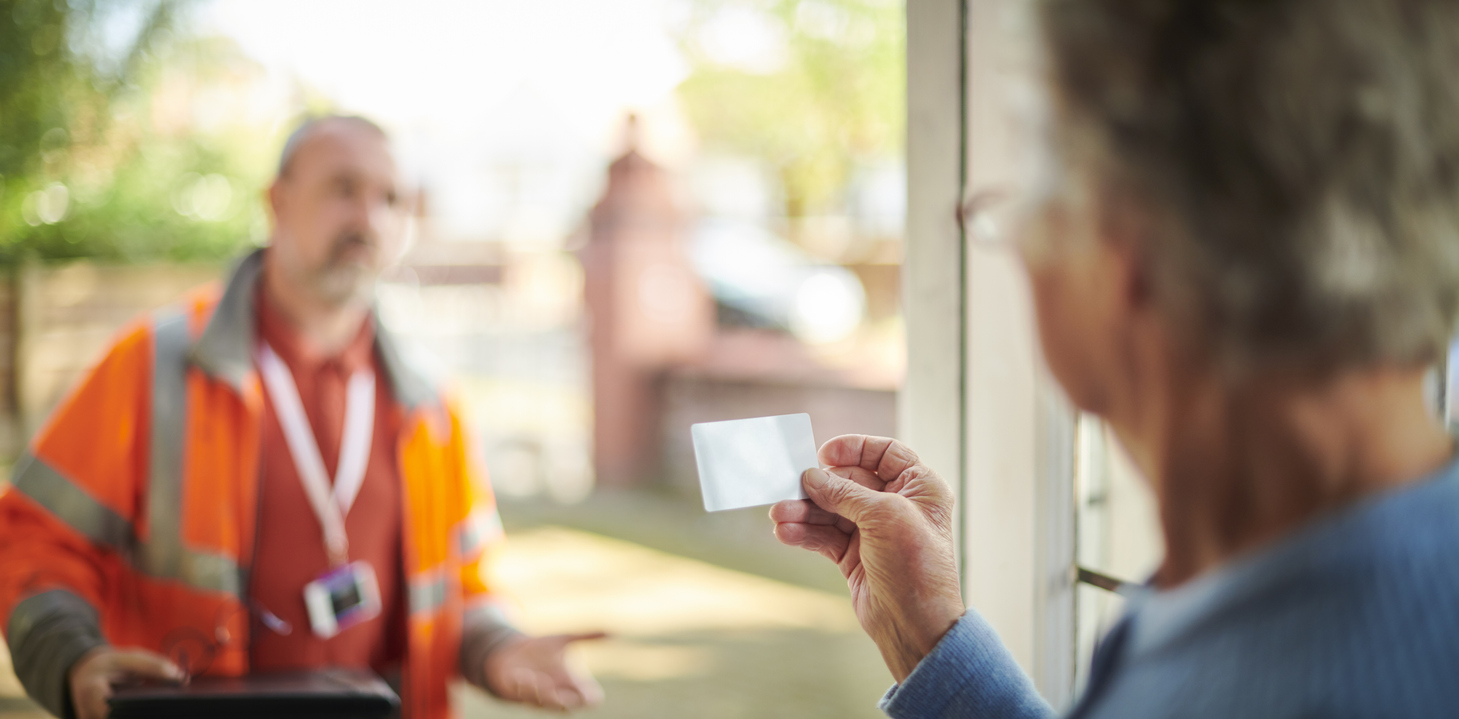 Woman checking ID card of tradesperson