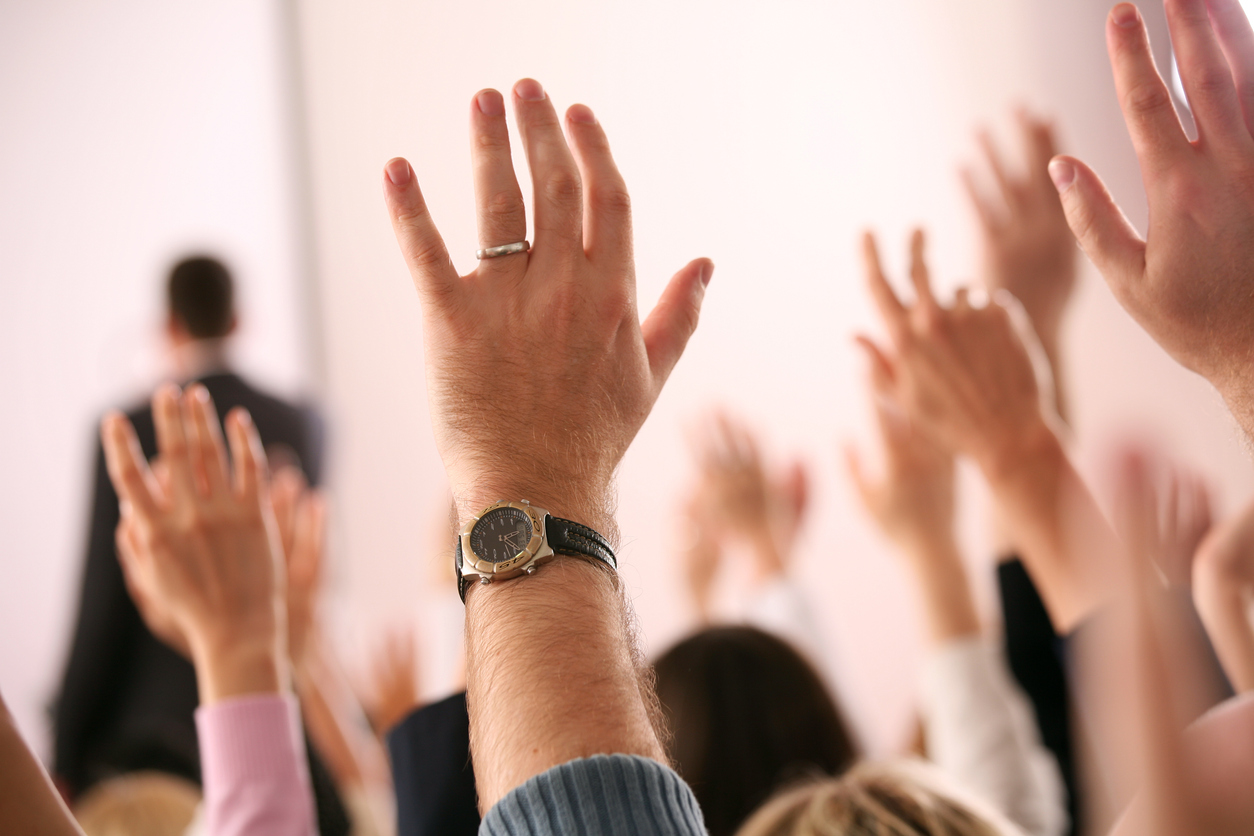 Business lecture with hands in the air.