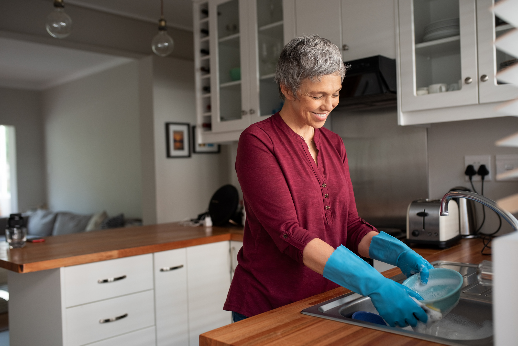 Senior woman washing dishes in her kitchen. Cheerful mature housewife in kitchen. Beautiful smiling woman with gray hair and blue gloves washing bowl in washbasin at home.