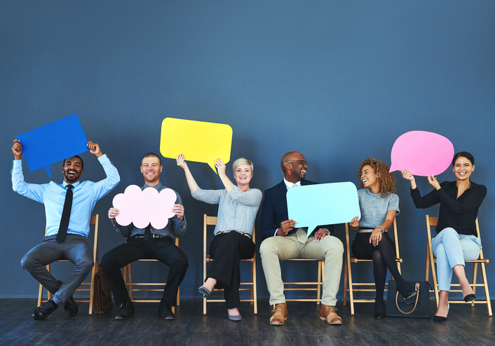 Shot of a group of people holding up speech bubbles against a blue background