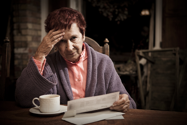 An elderly woman seated at the table with a cup of coffee distressed over the costs of her bills.