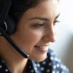 Close up head shot smiling friendly Indian woman wearing headset