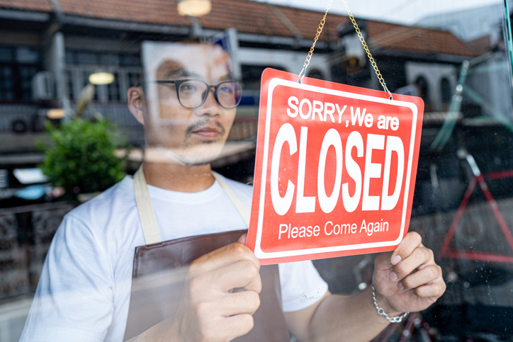 The owner of a small business shop puts up a closed sign in door window.