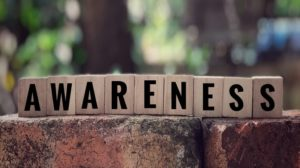 AWARENESS' word written on wooden blocks. With blurred vintage styled background.