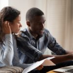 African Millennial couple sitting on sofa looking at bills