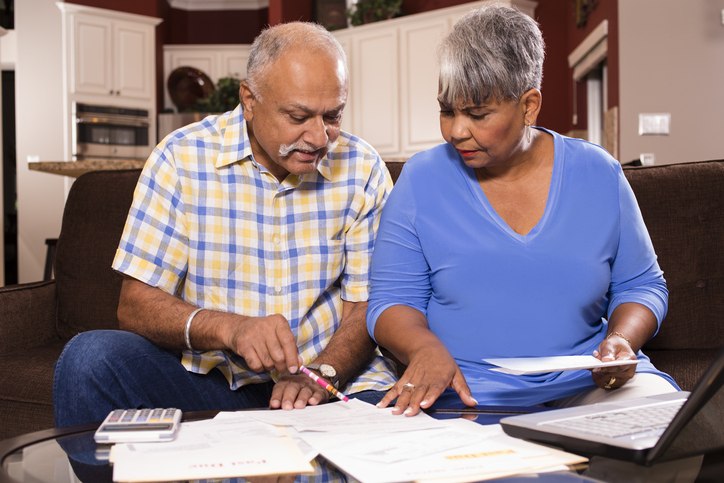 indian man and african woman looking at bills together in the home