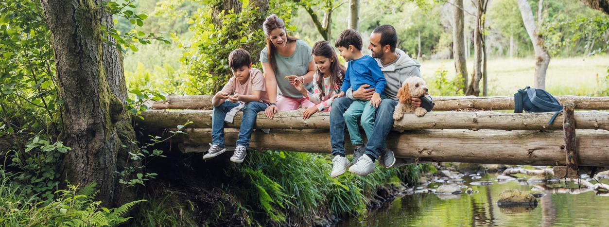 Family and dog sitting on bridge looking into river