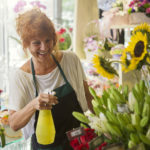 A female shop worker in a florist shop is watering flowers