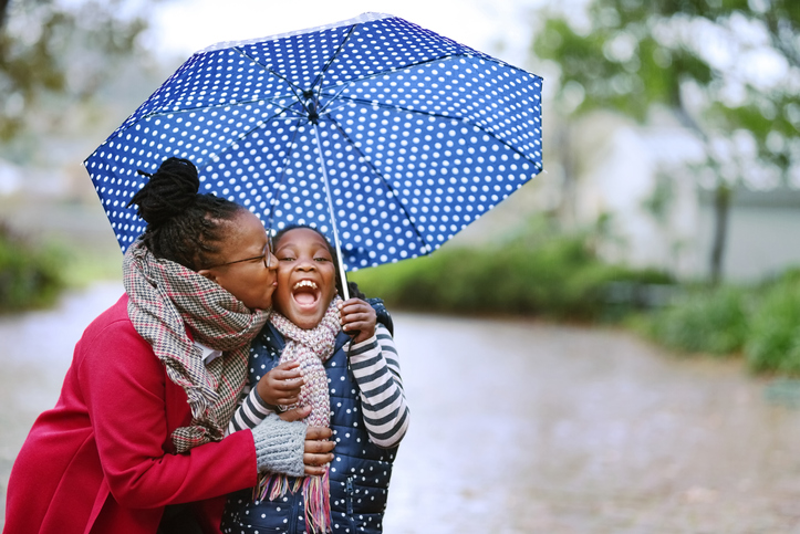 Picture of a black woman kissing her daughter while hiding from the rain under an umbrella