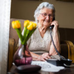 Old woman with gray white hair and glasses sitting talking on the phone.