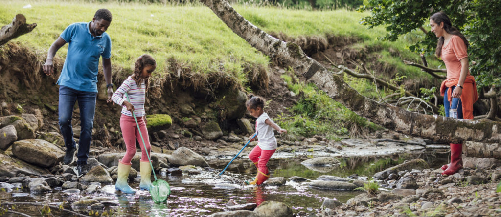 Family of four crossing a river together with their fishing rods.