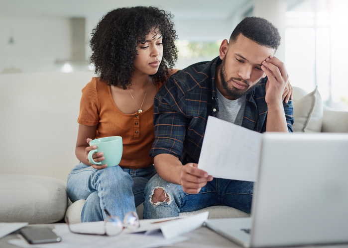 Couple sitting on sofa looking stressed over their bills