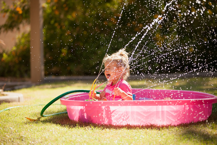 Little girl splashing in a pink kiddie pool with the hose and sprinkler spraying in her face.
