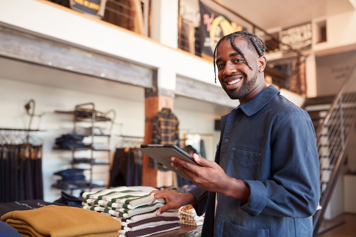 Portrait Of Male Owner Of Fashion Shop Using Tablet