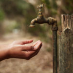 A woman holing her hands under an outdoor tap that is not running